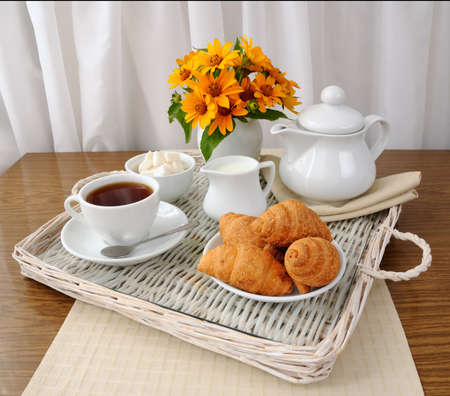 Breakfast with croissants with tea and milk on a tray photo