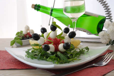 Mozzarella with cherry tomatoes and olives on a skewer with arugula and white wine photo