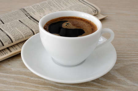 periodicals: A cup of freshly brewed coffee on the table with newspaper