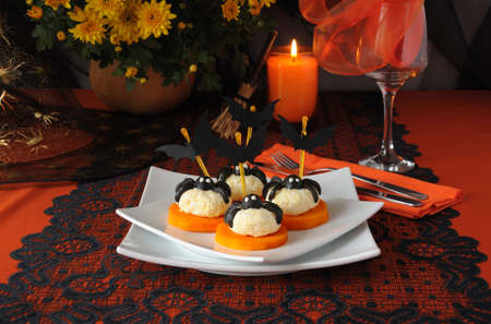 Cheese balls with olives spiders and bats on a festive table Standard-Bild
