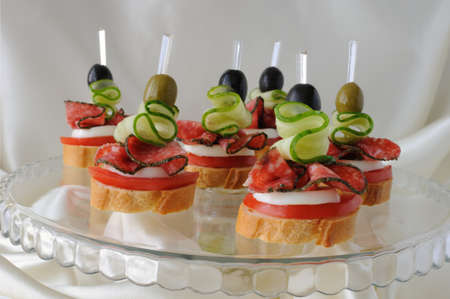 Canape of the baguette with salami on a glass base