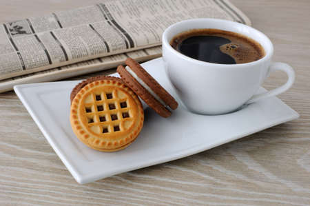 A cup of fresh brewed coffee and biscuits on the table with newspaper
