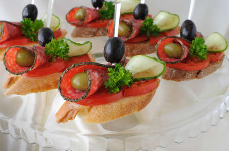 atilde: Sandwiches (canapés) of salami with olives on a plate Stock Photo