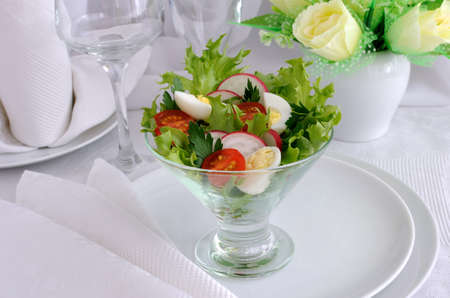 Salad of cherry tomatoes with quail egg and radish in the salad leaves photo