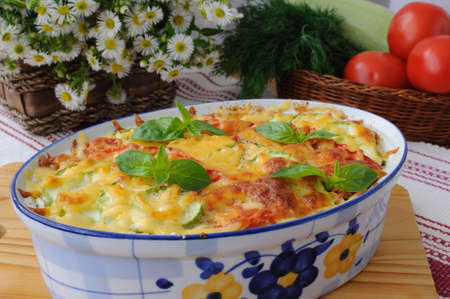 casserole of pasta with zucchini and tomato and cheese on the table