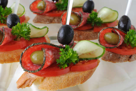 Sandwiches (canapés) of salami with olives on a plate Standard-Bild