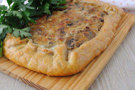 flaky: Tart with mushrooms in a creamy sauce with herbs close up