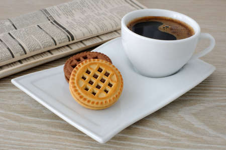 A cup of fresh brewed coffee and biscuits on the table with newspaper photo