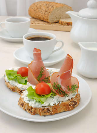 breakfast with a cup of coffee and a sandwich of whole grain bread with ricotta and ham photo