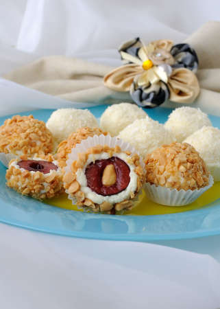 Cheese balls stuffed with cherries in peanuts and coconut flakes Standard-Bild