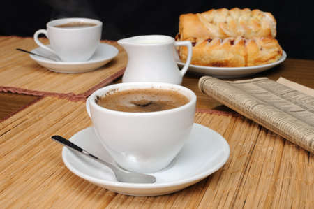milkman:  A cup of coffee with a newspaper on the table with the milkman and scones