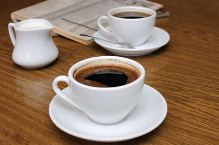 milkman: A cup of black coffee with a milkman on a table with newspaper