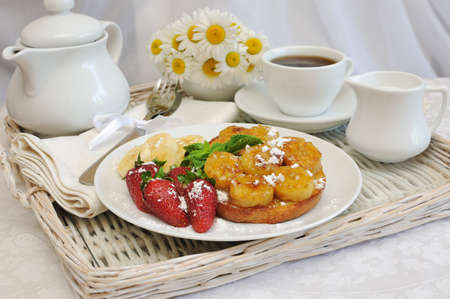 Breakfast with caramelized bananas and strawberries on a tray photo