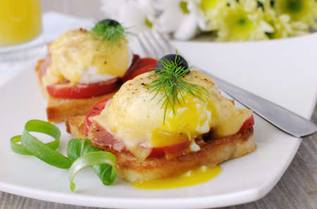 Eggs Benedict with ham and tomato on toast with cheese and orange juice Stock Photo