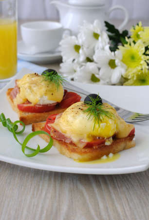 Eggs Benedict with ham and tomato and cheese on toast with orange juice and coffee