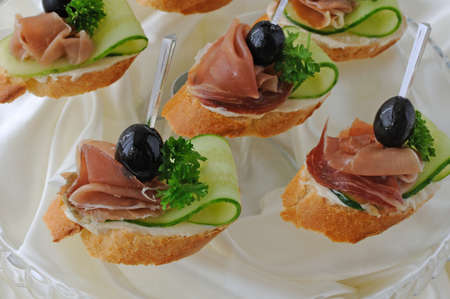 Mini sandwiches with ham and cucumber on a baguette photo