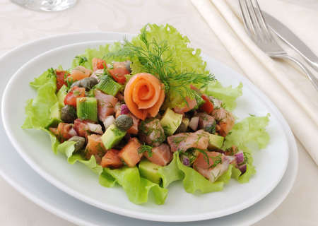 Avocado salad with tomatoes, smoked salmon and capers photo