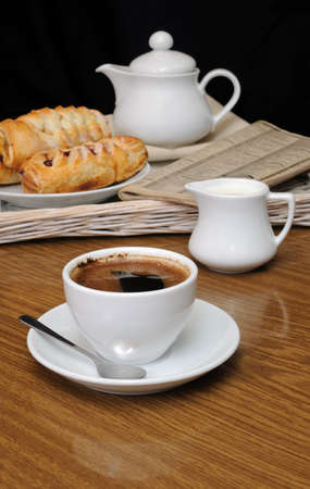 milkman: Cup of black coffee on the table with the milkman and biscuits on a tray with newspaper