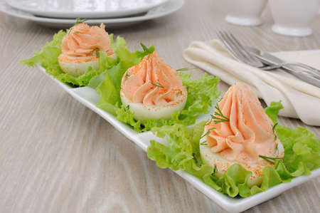 Eggs stuffed with pate salmon with red pepper in lettuce leaves