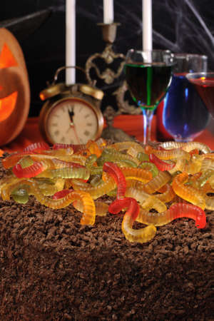 Chocolate cake with gelatin worms on the festive table in honor of Halloween photo