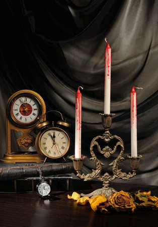 Bloody candles on the table with the clock and withered roses photo