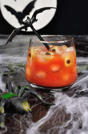 A glass of tomato juice with olives on ice