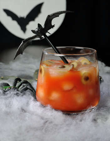 Glass of tomato juice with olives on ice for eyes etc.