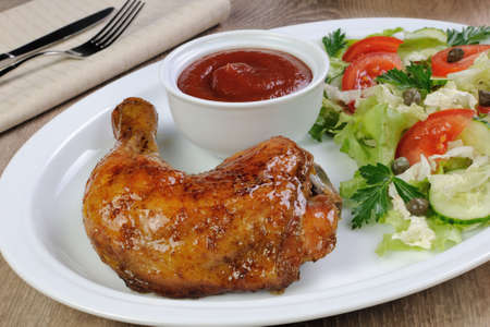 baked chicken: Baked chicken thigh with sauce and salad Stock Photo