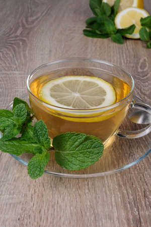 warming therapy: Cup of tea with a slice of lemon and  mint Stock Photo