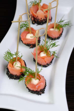 collation: Appetizer of mozzarella wrapped slice of salted salmon with sesame Stock Photo
