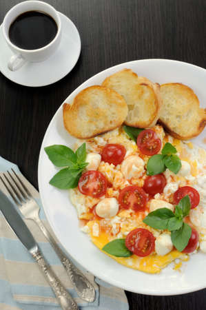 elevenses: Scrambled eggs with cherry tomatoes, mozzarella and croutons Stock Photo