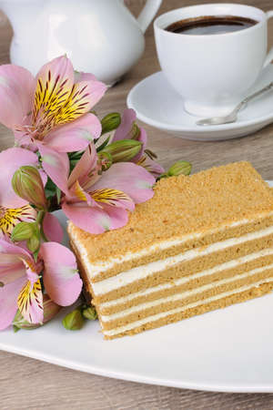 honey cake: Piece of honey cake with a cup of coffee on a table with a flower Stock Photo