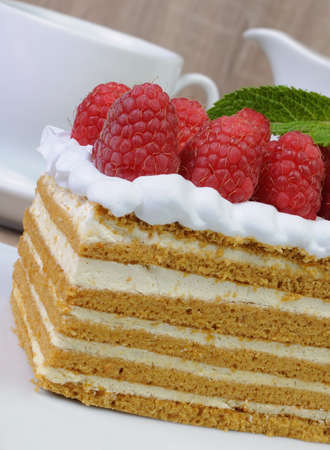 elevenses: Piece of honey cake with whipped cream and raspberries