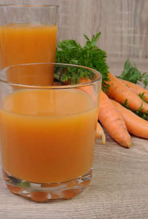 elevenses: glass of  carrot juice on the table with carrots
