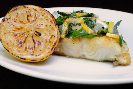 pike place: slice of baked fish perch with herbs and lemon slices