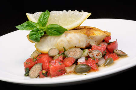 fresh water fish: slice of baked fish perch with vegetable garnish and lemon
