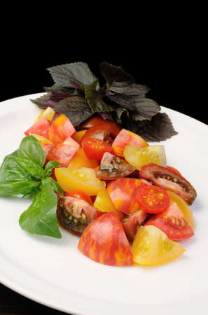 elevenses: slices of different varieties of tomato with basil on a plate Stock Photo