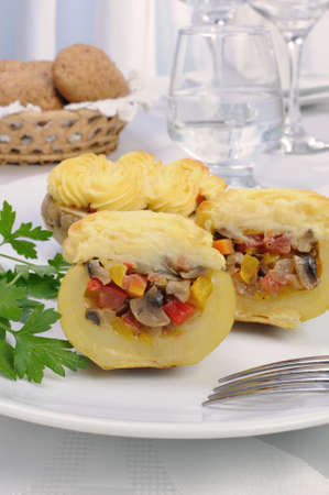 elevenses: Baked potatoes stuffed with vegetables on a platter Stock Photo