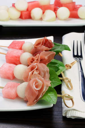 elevenses: Appetizer of ham with melon and watermelon and basil on a skewer