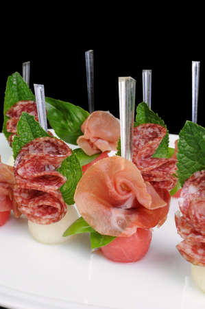 tidbit: Canape of watermelon balls with a melon with gammon and salami