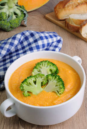 lunch hour: Pumpkin soup puree with cream in a dish with broccoli Stock Photo