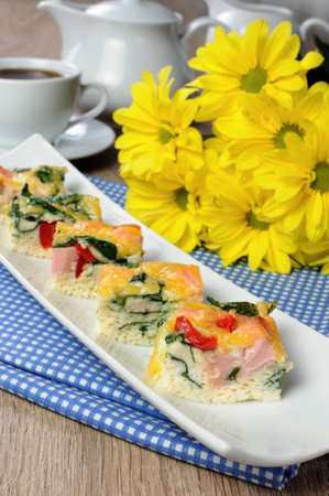 elevenses: Canape of omelet with spinach, sausage and a cup of coffee Stock Photo