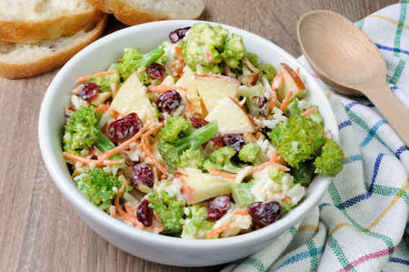 Salad of broccoli, carrots, apples, rice, cranberries and walnuts dressed with yogurt
