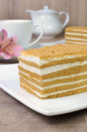 elevenses: Piece of honey cake with a cup of coffee on a table with a flower Stock Photo