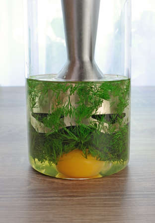 elevenses: olive oil, egg yolk, dill in a glass with immersion blender to prepare a creamy sauce