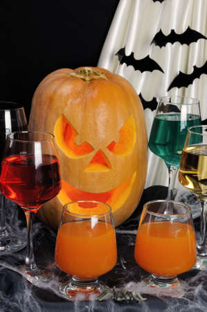 commemorate: Glasses with different drinks on the table in honor of Halloween