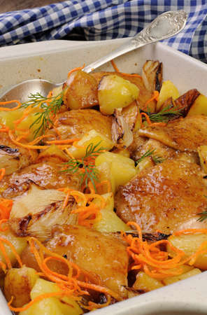 roasting pan: Braised roast chicken with potatoes, carrots and shalott in ceramic roasting pan