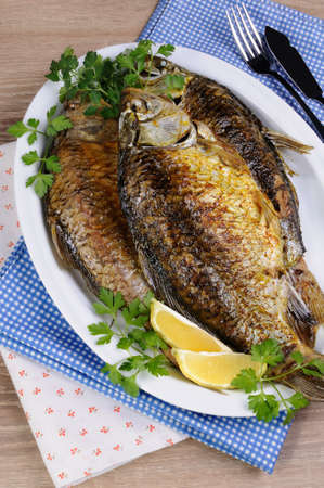 limnetic: Fried crucian carp in a plate on the table with napkins