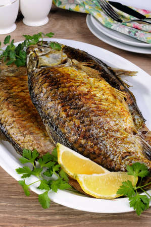 limnetic: Fried crucian carp in a plate on the table  closeup Stock Photo