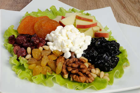 elevenses: Vitamin salad with nuts, apples, dried fruit and cottage cheese in lettuce leaves Stock Photo